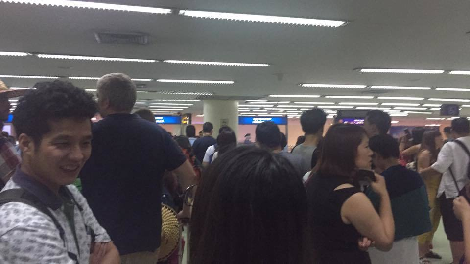 the crowded, hot and very slow moving immigration hall at the old airport in bangkok, avoid it